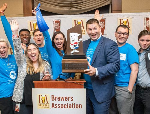 brewers association pose in front of trophy